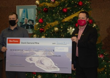 CIBC's Josh Firth accepts a cheque for $25,000 raised by participants in the Mud Bucket Challenge