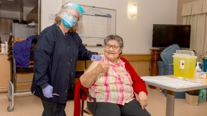Caroline Douglas receives a Covid-19 vaccination at Behchokǫ̀'s Jimmy Erasmus Seniors Home on December 31, 2020