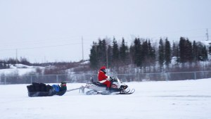 Santa arrives in Dettah on a snowmobile. Sarah Pruys/Cabin Radio