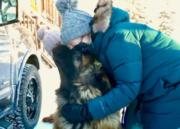 A hug for a dog in Norman Wells from an arriving member of the veterinary team
