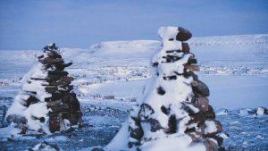Ulukhaktok is pictured beyond inukshuks overlooking the community in January 2021. Sarah Pruys/Cabin Radio