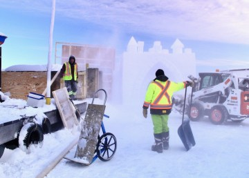 Workers at Yellowknife's Snowcastle build walls in January 2021