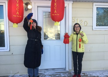 Xiaoyi Yan (left) and Angela Law, members of the Yellowknife Chinese Association, hold up lanterns that will serve as prizes for the Lantern Festival riddle contest