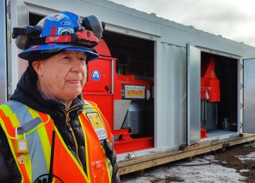 Clarence Pyke, Nechalacho's mine manager, in front of an ore sorting machine