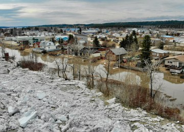 Ice and water breach the banks of the Mackenzie River and flow onto Fort Simpson streets on May 8, 2021