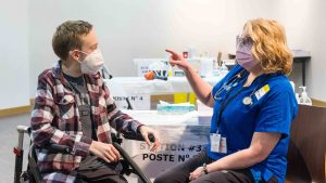 Riley Oldford, left, talks to a nurse practioner before becoming the first Yellowknife teenager to receive the Pfizer-BioNTech vaccine on May 6, 2021. Sarah Pruys/Cabin Radio