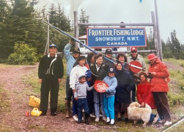 A photo from Shawna Yamkovy's family visit to the community of Łútsël K'é, then named Snowdrift, with Yamkovy in the middle wearing a black coat