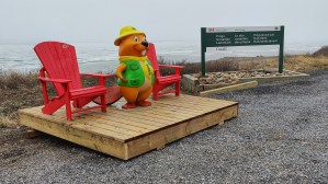 A Parks Canada beaver statue and red chairs by the Arctic Ocean at the Pingo Canadian Landmark in Tuktoyaktuk