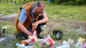 Dene National Chief Norman Yakeleya placing a flag at a grave in the Yellowknife cemetery. Luisa Esteban/ Cabin Radio.