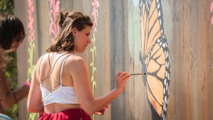 Maddy Tetreault painting a mural at Folk on the Rocks 2021. Sarah Pruys/ Cabin Radio.