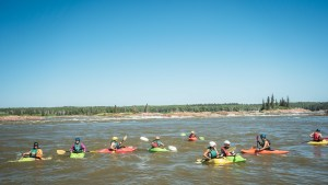 Kayakers at the Mountain Portage rapids during Slave River Paddlefest in August 2021. Sarah Pruys/Cabin Radio