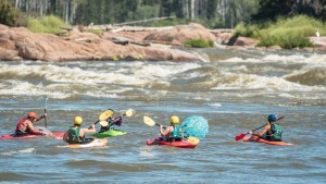 The beach ball race at the Mountain Portage rapids during Slave River Paddlefest in August 2021. Sarah Pruys/Cabin Radio