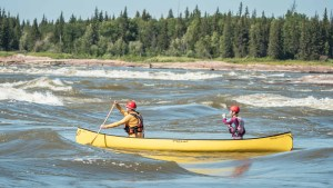 Canoers at the Mountain Portage rapids during Slave River Paddlefest in August 2021. Sarah Pruys/Cabin Radio