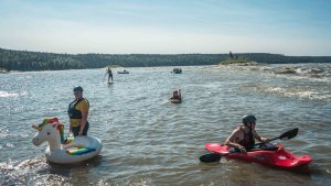 Paddlers at the Mountain Portage rapids during Slave River Paddlefest in August 2021. Sarah Pruys/Cabin Radio