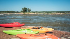 Kayaks at the Mountain Portage rapids during Slave River Paddlefest in August 2021. Sarah Pruys/Cabin Radio