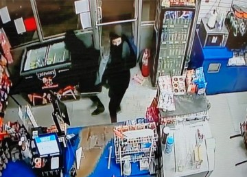 Two suspects are seen wearing dark grey and black clothing with facial coverings in an RCMP supplied photo.