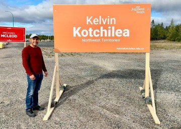 Kelvin Kotchilea stands beside election signs in early September 2021